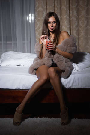 Sexy brunette on the bed sits and drinks a cocktail