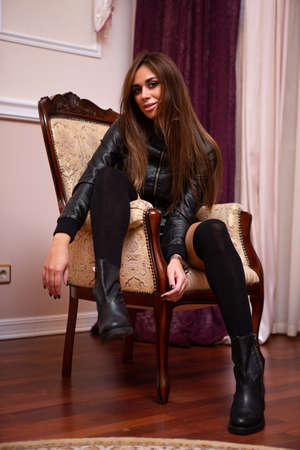 Cute brunette in black is sitting on a beautiful chair