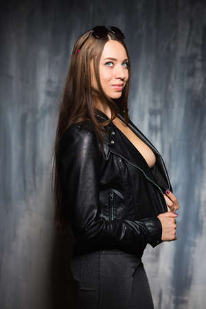 Portrait of sexy playful brunette posing in black jacket and jeans Stock Photo