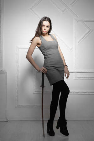 Charming brunette with a sword posing in a gray dress Stock Photo