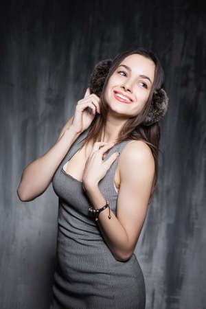 Smiling cute woman posing over gray background Stock Photo