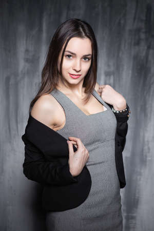 Glamorous young lady wearing grey clothes posing indoor Stock Photo