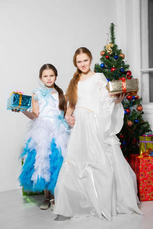 Girls with gifts posing against the background of the christmas tree Stock Photo