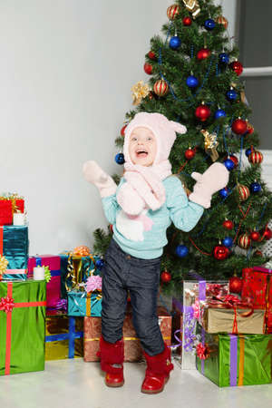 Little girl fooling around gifts and a christmas tree Stock Photo