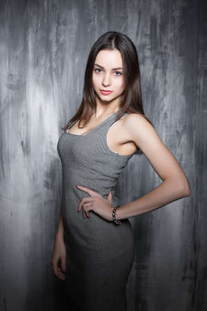 Playful young brunette wearing grey clothes posing near gray wall