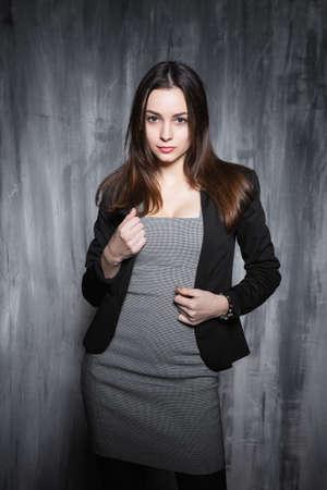 Portrait of a sexy brunette posing in a gray dress