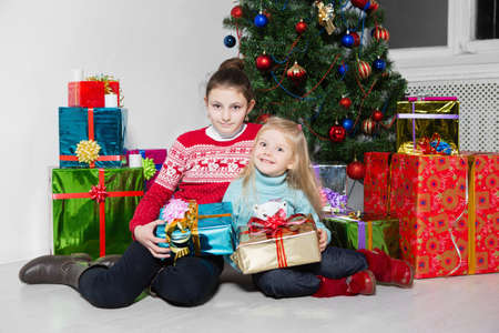 Two cute girls sitting near the gifts and the christmas tree Stock Photo