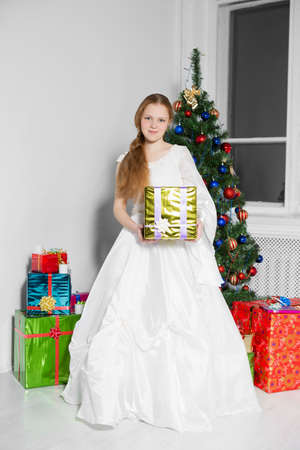 A girl in a white dress with a gift in her hands posing against the background of the christmas tree