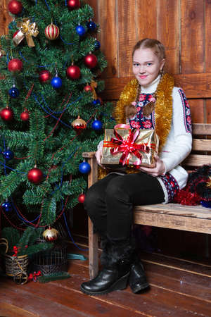 Cheerful girl sitting with gifts near the ?hristmas tree