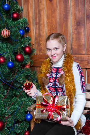 Beautiful happy girl near the new year tree with gifts Stock Photo