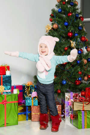 Little playful girl on the background of the christmas tree