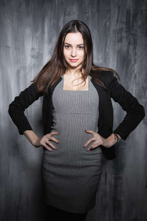 Portrait of a glamorous young brunette, standing near a gray wall