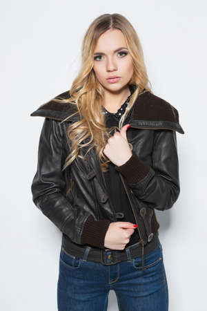 Portrait of a playful blonde in  jacket and jeans posing on a white background
