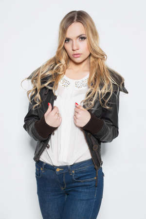 Portrait of elegance young blonde in  jacket and jeans posing on a white background
