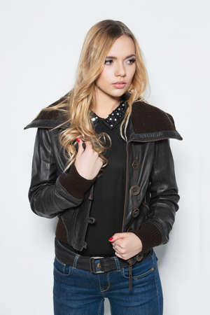 Portrait of a pensive blonde  in jacket and jeans posing on a white background Stock Photo