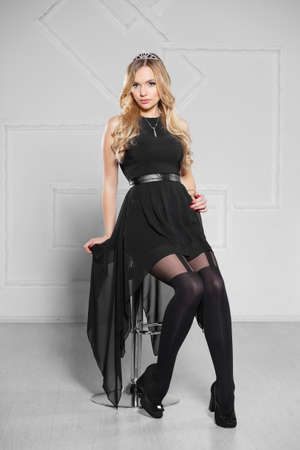 Sexy young blond woman posing in short black dress