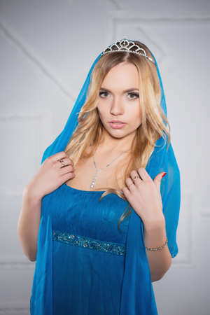Portrait of a beautiful lady posing in a blue dress and diadem