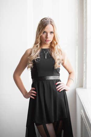 Portrait of lovely young woman wearing black dress  posing in studio