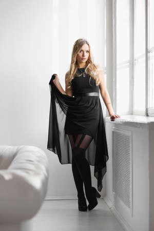 Pensive young woman wearing black dress  posing in studio