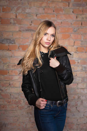Portrait of a beautiful woman in a jacket and jeans against the background of a wall Stock Photo