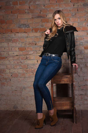 Sexy playful blonde in jeans posing against a brick wall.
