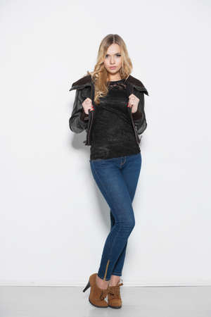 Beautiful young woman in a jacket and jeans posing against a white wall Stock Photo