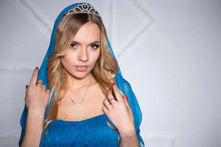 Portrait of a alluring lady posing in a blue dress and diadem