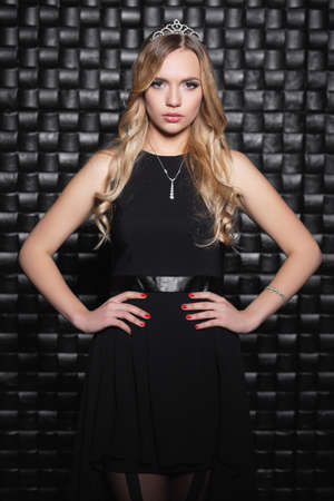 Portrait of a young woman posing in a black dress and tiara