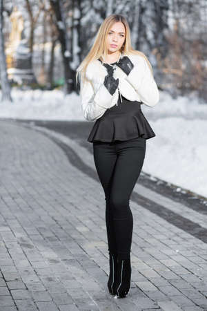 Charming young blonde in a white coat and tight pants posing on a snowy background in the park
