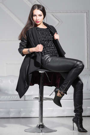 Young lovely lady posing in studio sitting on a chair and dressed in black clothes. 版權商用圖片