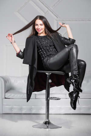 Young beautiful lady posing in studio sitting on a chair and dressed in black clothes. Standard-Bild