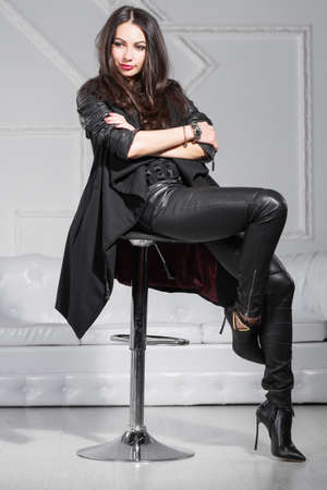 Young thoughtful lady posing in studio sitting on a chair and dressed in black clothes.