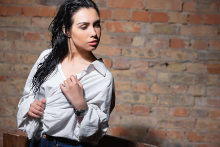 Portrait of a pretty woman in white shirt posing against a brick wall