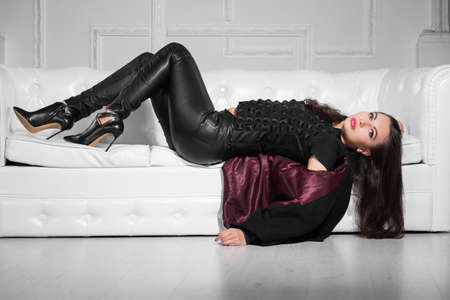 Nice young lady posing in studio lying on a white sofa and wearing black clothes