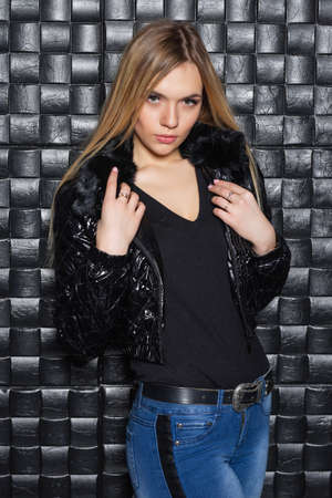 Portrait of a young woman posing in the studio near the black wall, wearing a black jacket and blue bonded jeans