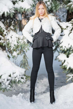 Young woman posing standing in winter among spruce in tight pants and white coat.