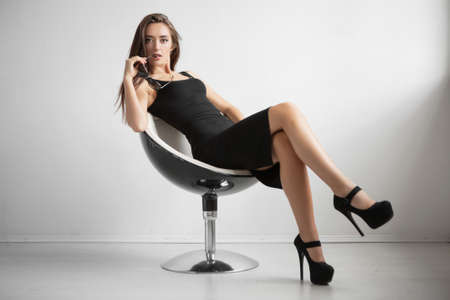 Attractive young lady posing sitting on a chair dressed in a black dress and shoes. Banco de Imagens - 117004268