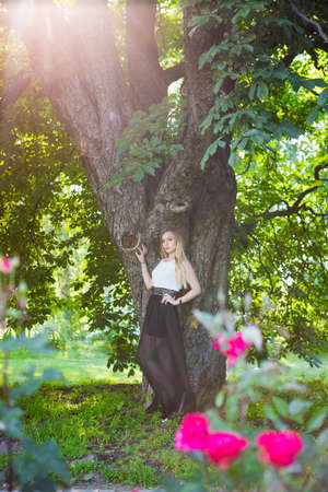 ?ute blonde woman posing in a park standing near a tree dressed in a long dress