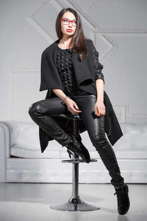 Young charming brunette in glasses posing in the studio sitting on a chair and dressed in black clothes