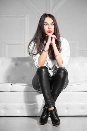 Attractive woman posing sitting on a sofa in a studio, dressed in a white shirt and black pants Stock Photo