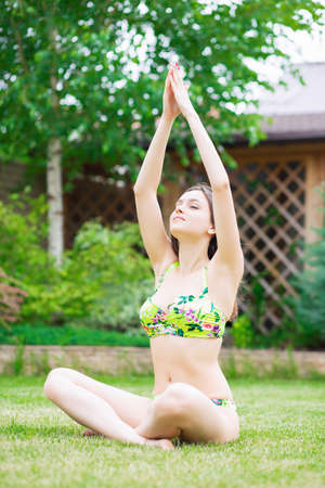 Beautiful young brunette dressed in a colorful swimsuit posing in the summer outdoors sitting on the grass Stock Photo