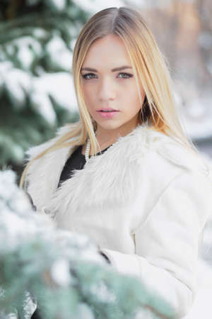 Portrait of a thoughtful blonde posing in winter among fir trees in a black suit and white coat
