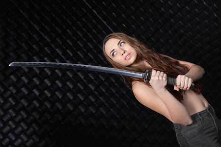 Portrait of thoughtful woman with katana in hand posing on black background Imagens