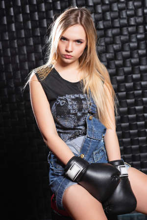 Portrait of a serious woman posing in the studio on a black background in boxing gloves, dressed in overalls and a t-shirt.