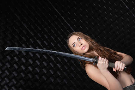 Portrait of a young woman with a katana in her hands posing on a black background