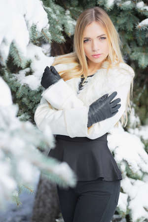 Portrait of a young blonde posing in winter among firs in a black suit and white coat