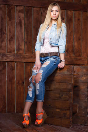 Pensive young blonde posing in  studio dressed in denim blue clothes, a t-shirt and shod in slingbacks