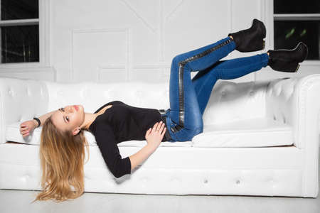 Perfect young woman posing lying on the sofa in the studio, dressed in a black  t-shit and jeans Stock Photo