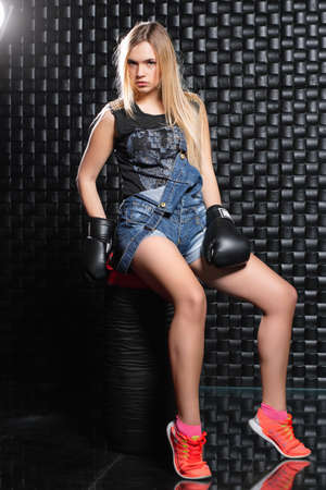 Charming woman posing sitting on a punching bag in boxing gloves, dressed in overalls and a t-shirt. Stock Photo