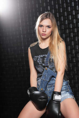 Beautiful young woman posing dressed in denim overalls, t-shirt and boxing gloves